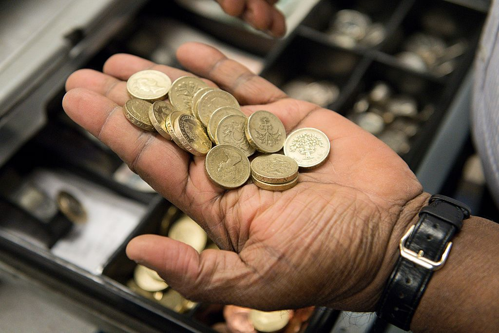 """A worker sorts pound coins taken from a cash register in a convenience store in London on October 7, 2016. The Bank of England is """"looking into"""" what caused the pound to slump more than six percent against the dollar in less than ten minutes Friday, a spokesman told AFP. / AFP / JUSTIN TALLIS (Photo credit should read JUSTIN TALLIS/AFP/Getty Images)"""
