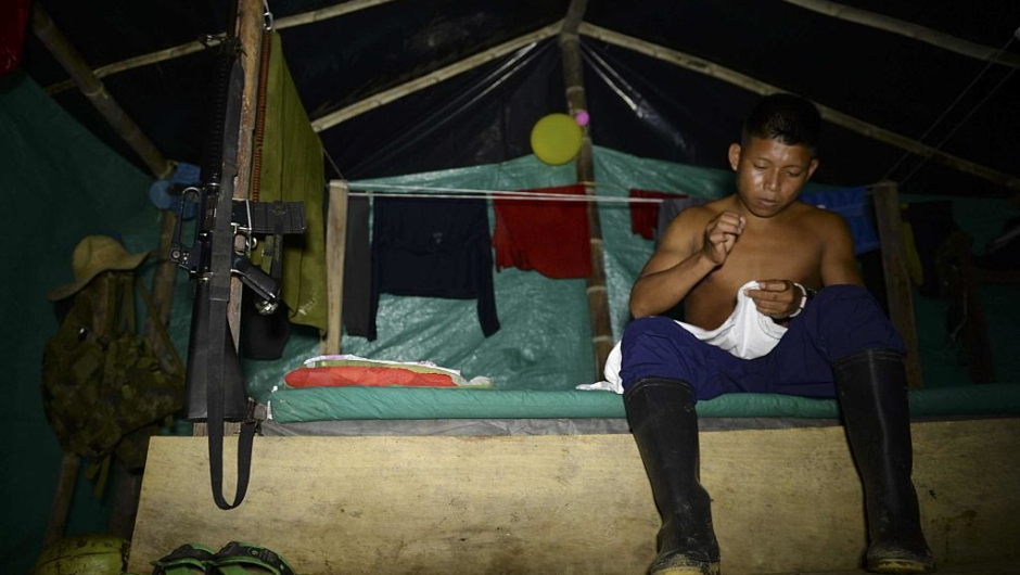 A FARC guerillas member prepares his shirt at the 34 Alberto Martinez camp front just days before their demobilization to the final concentration zones, in Vegaez municipality, Antioquia department, Colombia on December 30, 2016. The Colombian government signed a final peace agreement with the FARC guerrilla on November 26 to be implemented within the next six months, during which FARC members will give up their weapons and start their transition to be reintegrated into society. / AFP / STR / RAUL ARBOLEDA (Photo credit should read RAUL ARBOLEDA/AFP/Getty Images)