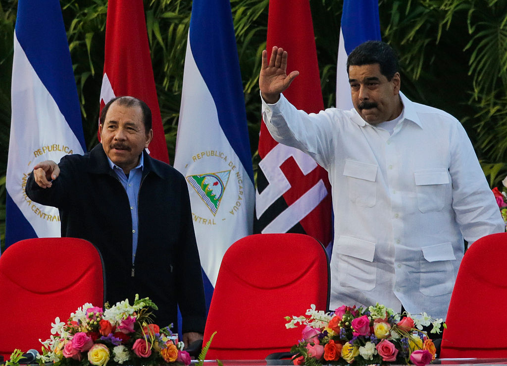 Nicaraguan President Daniel Ortega (L) and Venezuelan President Nicolas Maduro (R) greet supporters during the inauguration ceremony for his fourth term in office in Managua on January 10, 2017. / AFP / INTI OCON (Photo credit should read INTI OCON/AFP/Getty Images)