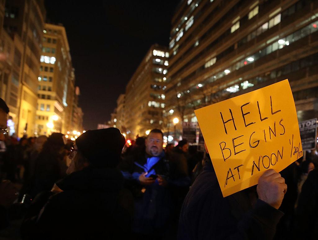 """Un manifestante en Washington, protestaba en la noche del 19 de enero con un cartel que dice """"El infierno empieza el 20/01/2017"""". (Crédito: Mark Wilson/Getty Images)"""