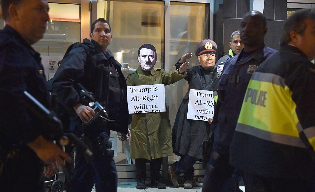 """Dos hombres con máscaras de Adolfo Hitler y Benito Mussolini protestan en Washington haciendo el saludo nazi con carteles que dicen """"Trump está de bien nosotros"""", mientras policías vigilan la seguridad del lugar. (Crédito: PAUL J. RICHARDS/AFP/Getty Images)"""
