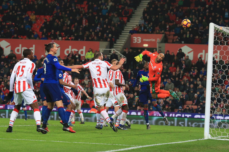 El balón impulsado por Wayne Rooney vence la resistencia del golero Lee Grant (d) del Stoke City, durante el partido de la Liga Premier del pasado sábado. (Crédito: LINDSEY PARNABY/AFP/Getty Images)