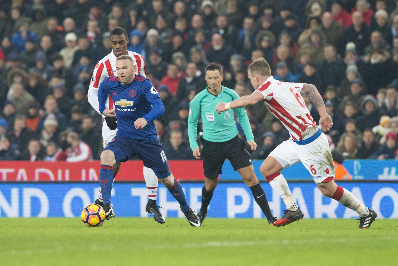 Wayne Rooney (i) disputa el balón con Glenn Whelan, del Stoke City, durante el partido de la Liga Premier del sábado pasado en Stoke-On-Trent. (Crédito: Roland Harrison/Action Plus via Getty Images)