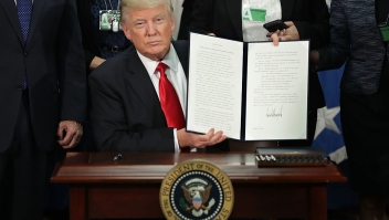 WASHINGTON, DC - JANUARY 25: (AFP OUT) U.S. President Donald Trump (C) displays one of the four executive orders he signed during a visit to the Department of Homeland Security January 25, 2017 in Washington, DC. Trump signed four executive orders related to domestic security and to begin the process of building a wall along the U.S.-Mexico border. (Photo by Chip Somodevilla/Getty Images)