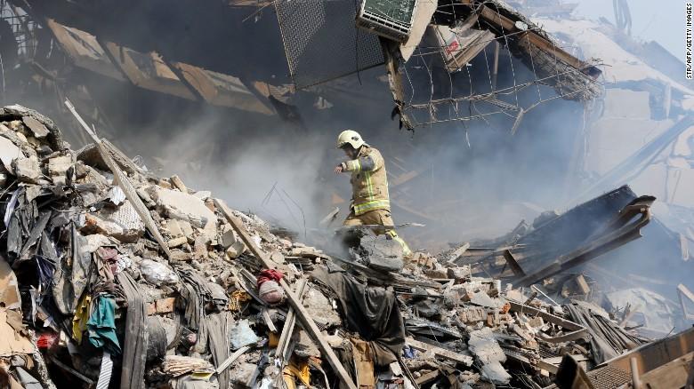 Un bombero iraní camina sobre los escombros que dejó el derrumbe del edificio de Plasco.