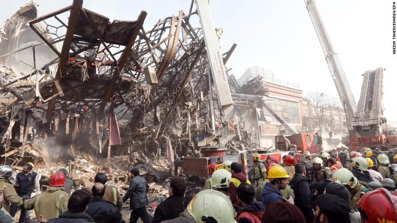 Las autoridades alrededor de los  escombros del edificio, que era uno de los más antiguos de Teherán.