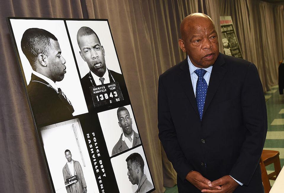El congresista e ícono de los derechos civiles en Estados Unidos John Lewis, en una imagen de noviembre de 2016 junto a fotografías de su arresto por una protesta en 1963. (Rick Diamond/Getty Images)