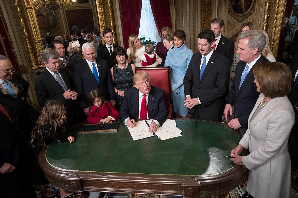 El presidente Donald Trump acompañado de los líderes del Congreso y su familia, mientras firma oficialmente sus nominaciones al gabinete en la Sala Presidencial del Senado del Capitolio.