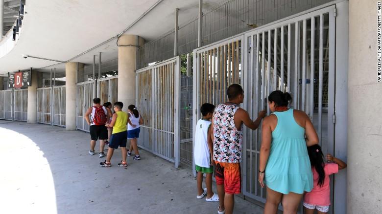 Turistas miran a través de las entradas principales del estadio.