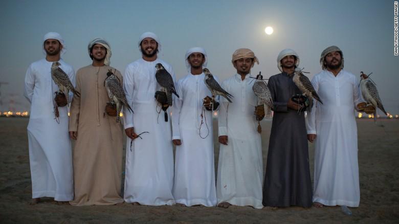 Hombres emiratíes posan con sus halcones tras una sesión de entrenamiento.