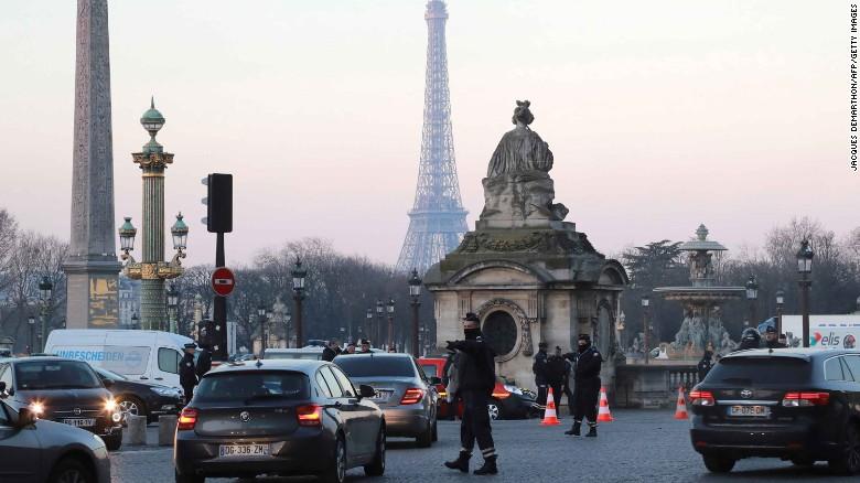 Un policía regula el tráfico en París, donde las restricciones al tráfico vehicular buscan ponerle un freno a la contaminación.