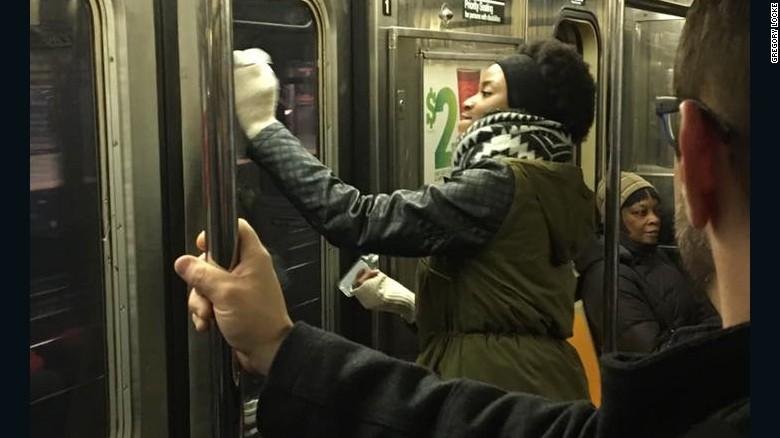Una pasajera ayuda a remover el graffiti del tren.