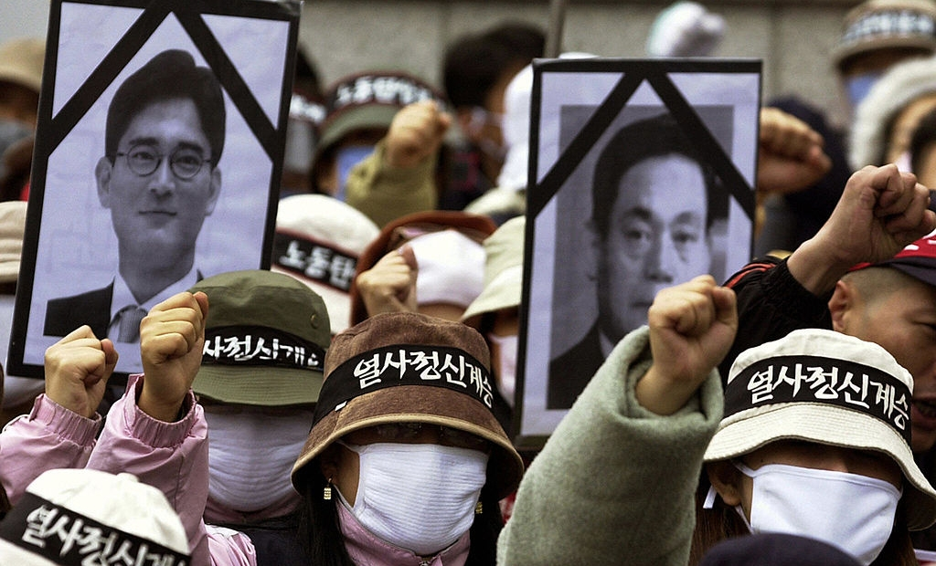 EOUL, REPUBLIC OF KOREA: South Korean workers chant slogan and hold black ribbon pictures of Lee Kun Hee (R) Chairman of the Samsung Group and his son Lee Jae-Yong (L) during a protest rally in Seoul, 12 November 2003. Tens of thousands of workers launched a one-day nationwide strike Wednesday as militant labor union leaders violated a police ban to stage a protest rally against government policy. The Korean Confederation of Trade Unions (KCTU) said some 150,000 workers joined the stoppage at 120 workplaces, including South Korea's largest auto company, Hyundai Motor, in the southern city of Ulsan.The labor ministry said the walkout had no major impact on the economy, saying it 44,000 workers from 77 metal, textile and chemical firms across the country.AFP PHOTO/JUNG YEON-JE (Photo credit should read JUNG YEON-JE/AFP/Getty Images)