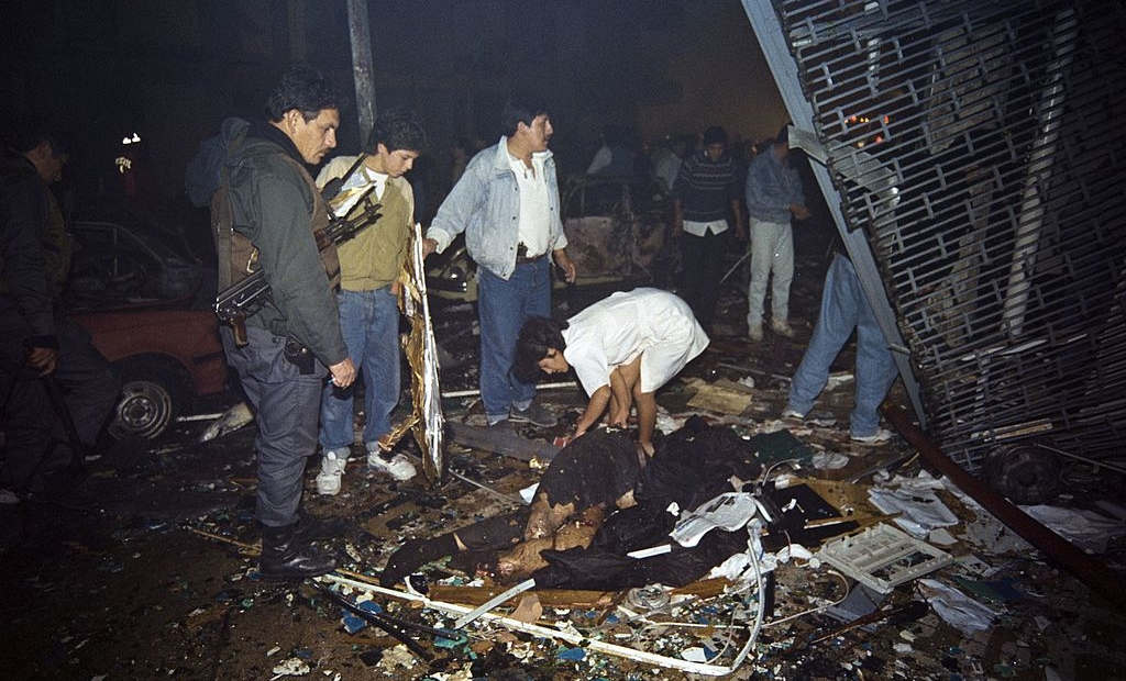A woman examines the remains of a victim killed late July 16, 1992 in a car bomb attack in the Miraflores residential neighborhood, in Lima. At least 15 people were killed and as many as 250 injured in the attack, which police say was the respopnsibility of the Shining Path guerillas. AFP PHOTO HERTOR MATA (Photo credit should read HECTOR MATA/AFP/Getty Images)