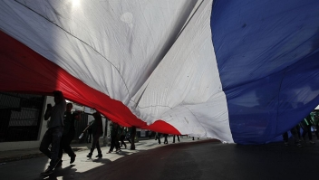 People hold a large Paraguayan flag during a demonstration against a new tax law, in Asuncion on October 19, 2015. The protesters, who are owners and employees from about 300 cooperative businesses, said that they are demonstrating against a new law that establishes a value-added tax of 10 percent to their services. AFP PHOTO / NORBERTO DUARTE (Photo credit should read NORBERTO DUARTE/AFP/Getty Images)