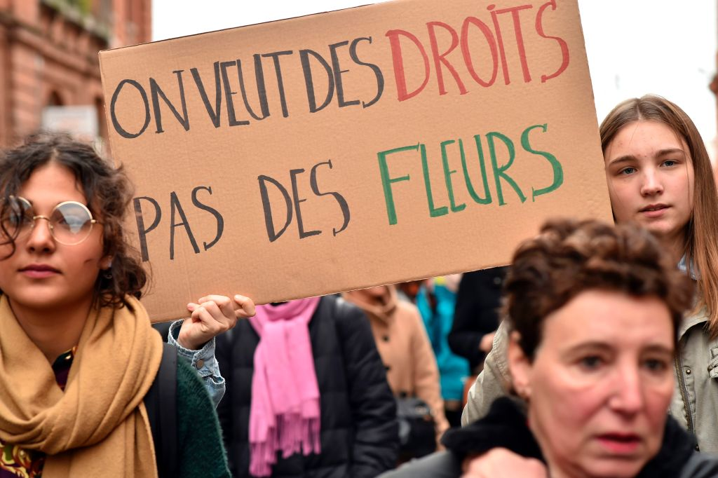 """A woman carries a sign reading """"We want rights, not flowers"""" during a demonstration march on March 8, 2017 in Toulouse, as part of International Women's Day. / AFP PHOTO / REMY GABALDA (Photo credit should read REMY GABALDA/AFP/Getty Images)"""