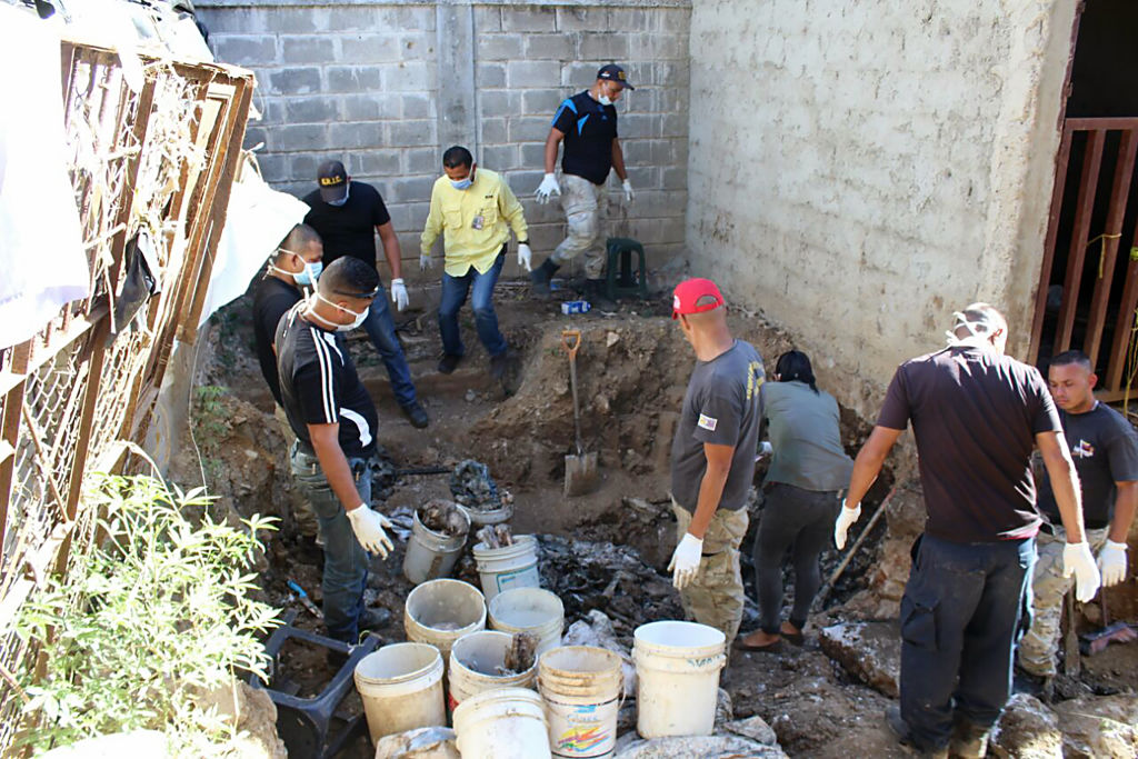 Forensic personnel study the remains of bodies discovered in the General Penitentiary of Venezuela, which had been closed down, in San Juan de los Morros, Guarico state, on March 10, 2017. On October 28, 2016 the government finished transferring the inmates of the General Penitentiary of Venezuela (PGV), a maximum-security prison in San Juan de Los Morros in the central state of Guarico, to a new facility after weeks of fighting between inmates for control of the prison and protests about the death of prisoners due to shortages of food and medicines. / AFP PHOTO / Juan BARRETO (Photo credit should read JUAN BARRETO/AFP/Getty Images)