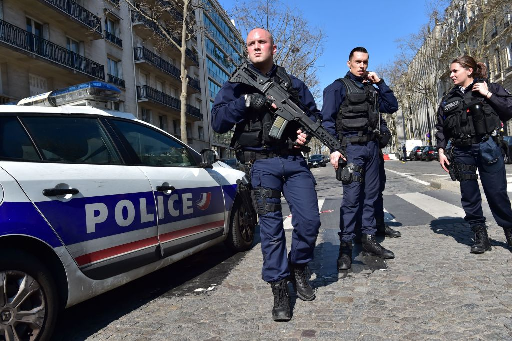 """French Police officers secure the scene near the Paris offices of the International Monetary Fund (IMF) on March 16, 2017 in Paris, after a letter bomb exploded in the premises. An employee at the Paris offices of the International Monetary Fund suffered injuries to her hands and face after opening a letter which exploded on March 16, police said. Several people were evacuated from the building near the Arc de Triomphe monument """"as a precaution"""", a police source said. / AFP PHOTO / CHRISTOPHE ARCHAMBAULT (Photo credit should read CHRISTOPHE ARCHAMBAULT/AFP/Getty Images)"""