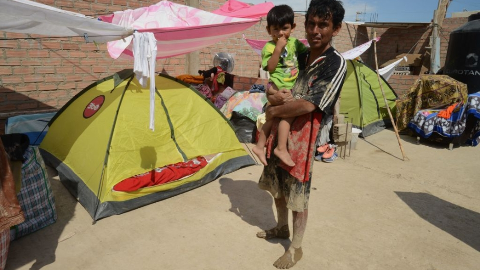 Families set up tents in the town of Huarmey, 300 kilometres north of Lima, where the ground was covered on March 19, 2017 with several centimetres of mud and silt after a flash flood hit the evening before. The El Nino climate phenomenon is causing muddy rivers to overflow along the entire Peruvian coast, isolating communities and neighbourhoods. Thousands have been affected since January, and 72 people have died. Most cities face water shortages as water lines have been compromised by mud and debris. / AFP PHOTO / CRIS BOURONCLE (Photo credit should read CRIS BOURONCLE/AFP/Getty Images)