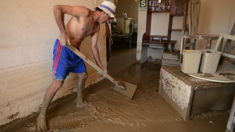 Local residents of the town of Huarmey, 300 kilometres north of Lima, try to get rid of muddy water on March 19, 2017 after a flash flood hit the evening before. The El Nino climate phenomenon is causing muddy rivers to overflow along the entire Peruvian coast, isolating communities and neighbourhoods. Thousands have been affected since January, and 72 people have died. Most cities face water shortages as water lines have been compromised by mud and debris. / AFP PHOTO / CRIS BOURONCLE (Photo credit should read CRIS BOURONCLE/AFP/Getty Images)