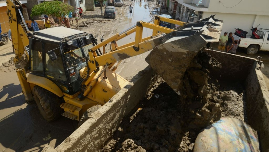 A bulldozer removes mud in the town of Huarmey, 300 kilometres north of Lima, on March 19, 2017 after a flash flood hit the evening before. The El Nino climate phenomenon is causing muddy rivers to overflow along the entire Peruvian coast, isolating communities and neighbourhoods. Thousands have been affected since January, and 72 people have died. Most cities face water shortages as water lines have been compromised by mud and debris. / AFP PHOTO / CRIS BOURONCLE (Photo credit should read CRIS BOURONCLE/AFP/Getty Images)