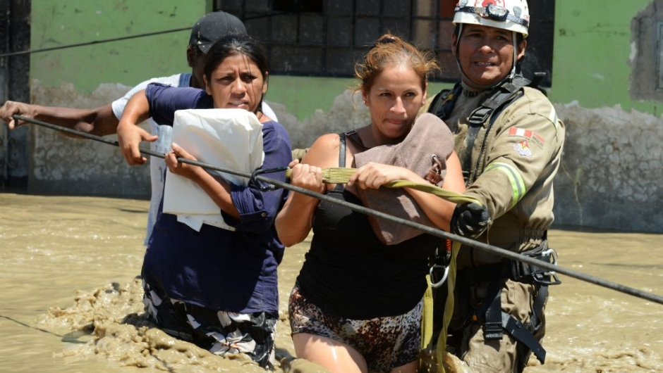 Rescuers help local residents of the town of Huarmey, 300 kilometres north of Lima, wade through muddy water in the street on March 19, 2017 after a flash flood hit the evening before. The El Nino climate phenomenon is causing muddy rivers to overflow along the entire Peruvian coast, isolating communities and neighbourhoods. Thousands have been affected since January, and 72 people have died. Most cities face water shortages as water lines have been compromised by mud and debris. / AFP PHOTO / CRIS BOURONCLE (Photo credit should read CRIS BOURONCLE/AFP/Getty Images)