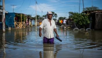 "TOPSHOT - A local resident wades through water on a street in the ""El Indio"" settlement on the outskirts of Piura, in northern Peru, on March 23, 2017. The El Nino climate phenomenon is causing muddy rivers to overflow along the entire Peruvian coast, isolating communities and neighbourhoods. / AFP PHOTO / Ernesto BENAVIDES (Photo credit should read ERNESTO BENAVIDES/AFP/Getty Images)"