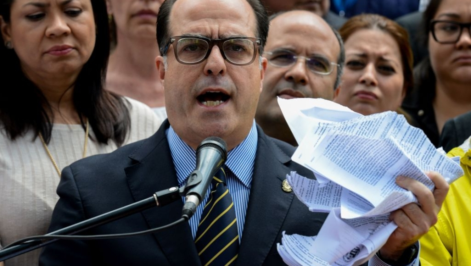 "The president of Venezuela's National Assembly Julio Borges, holds a tore copy of a sentence from Venezuela's Supreme Court granting itself legislative powers, as he speaks during a press conference in Caracas on March 30, 2017. Venezuela's Supreme Court took over legislative powers Thursday from the opposition-majority National Assembly, whose speaker accused leftist President Nicolas Maduro of staging a ""coup."" / AFP PHOTO / FEDERICO PARRA (Photo credit should read FEDERICO PARRA/AFP/Getty Images)"
