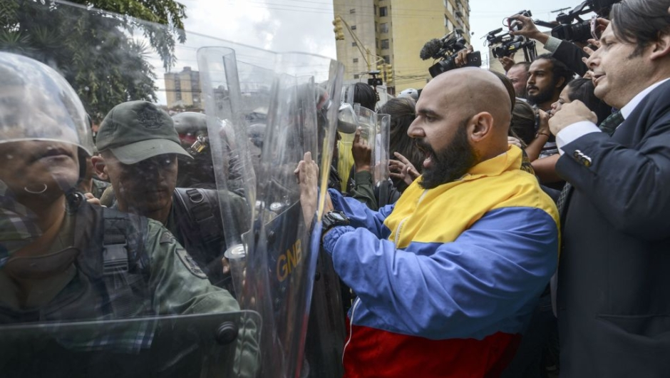 "OPSHOT - CORRECTION - Venezuelan opposition deputy Marco Bozo (C) scuffles with National Guard personnel in riot gear during a protest in front of the Supreme Court in Caracas on March 30, 2017. Venezuela's Supreme Court took over legislative powers Thursday from the opposition-majority National Assembly, whose speaker accused leftist President Nicolas Maduro of staging a ""coup."" / AFP PHOTO / JUAN BARRETO / The erroneous mention[s] appearing in the metadata of this photo by JUAN BARRETO has been modified in AFP systems in the following manner: [Marco Bozo] instead of [Carlos Bozo]. Please immediately remove the erroneous mention[s] from all your online services and delete it (them) from your servers. If you have been authorized by AFP to distribute it (them) to third parties, please ensure that the same actions are carried out by them. Failure to promptly comply with these instructions will entail liability on your part for any continued or post notification usage. Therefore we thank you very much for all your attention and prompt action. We are sorry for the inconvenience this notification may cause and remain at your disposal for any further information you may require. (Photo credit should read JUAN BARRETO/AFP/Getty Images)"