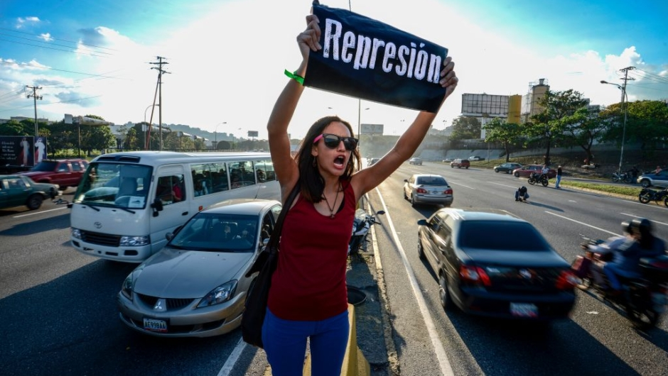 "A student shouts slogans against Venezuelan President Nicola Maduro during a protest on the main highway in Caracas on March 30, 2017. Venezuela's Supreme Court took over legislative powers Wednesday from the opposition-majority National Assembly, whose speaker accused leftist President Nicolas Maduro of staging a ""coup."" / AFP PHOTO / Juan BARRETO (Photo credit should read JUAN BARRETO/AFP/Getty Images)"