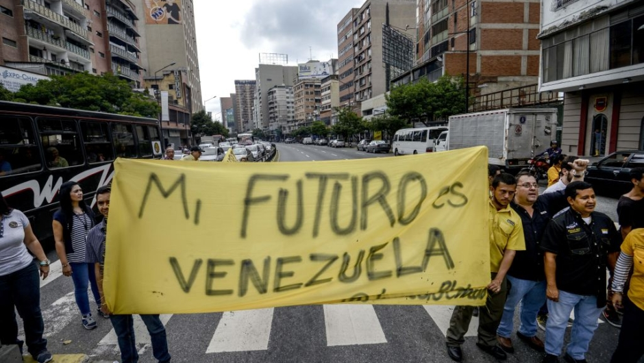 "Venezuelan opposition activists march along a street of Caracas on March 31, 2017 chanting slogans against the government of President Nicolas Maduro and deploying a banner that reads ""My Future Is Venezuela"". Venezuela's Supreme Court took over legislative powers Thursday from the opposition-majority National Assembly, whose speaker accused leftist President Nicolas Maduro of staging a ""coup."" / AFP PHOTO / Juan Barreto (Photo credit should read JUAN BARRETO/AFP/Getty Images)"