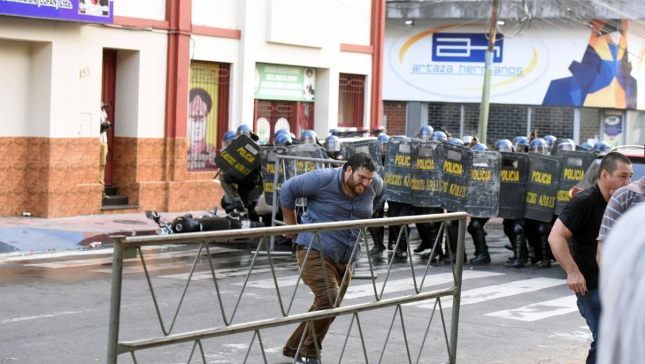 "Riot police crack down on a protest against the approval of a constitutional amendment for presidential reelection, outside Congress in Asuncion, on March 31, 2017. Ruling Colorado party senators and their allies, in a so-called ""parallel Senate"", unexpectedly approved an amendment Friday that would allow President Horacio Cartes to run for reelection in 2018, triggering protests that led to clashes between opposition demonstrators and the police. / AFP PHOTO / NORBERTO DUARTE (Photo credit should read NORBERTO DUARTE/AFP/Getty Images)"