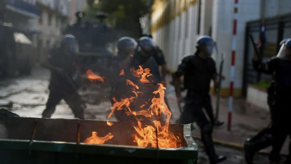 """Riot police crack down on a protest against the approval of a constitutional amendment for presidential reelection, outside Congress in Asuncion, on March 31, 2017. Ruling Colorado party senators and their allies, in a so-called """"parallel Senate"""", unexpectedly approved an amendment Friday that would allow President Horacio Cartes to run for reelection in 2018, triggering protests that led to clashes between opposition demonstrators and the police. / AFP PHOTO / NORBERTO DUARTE (Photo credit should read NORBERTO DUARTE/AFP/Getty Images)"""