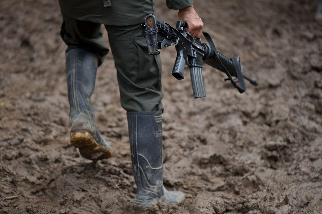 """TOPSHOT - A member of the Revolutionary Armed Forces of Colombia (FARC) guerrilla carries his rifle at the """"Alfonso Artiaga"""" Front 29 FARC encampment in a rural area of Policarpa, department of Narino in southwestern Colombia, on January 16, 2017. The UN is overseeing the FARC's disarmament as part of a peace deal the leftist guerrillas signed with the government to end a more than five-decade conflict. The FARC's 5,700 fighters are now in camps waiting to be transferred to UN-monitored ZVTN transitional zones where they will demobilize and begin their path to civilian life and legality over a period of six months. But the delay in setting up the camps has hindered their transfer to these areas. / AFP / LUIS ROBAYO (Photo credit should read LUIS ROBAYO/AFP/Getty Images)"""