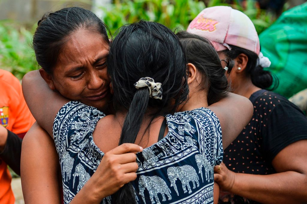 A woman cries when she is reunited with her family amidst the rubble left by mudslides following heavy rains in Mocoa, Putumayo department, southern Colombia on April 2, 2017. The death toll from a devastating landslide in the Colombian town of Mocoa stood at around 200 on Sunday as rescuers clawed through piles of muck and debris in search of survivors. / AFP PHOTO / LUIS ROBAYO (Photo credit should read LUIS ROBAYO/AFP/Getty Images)