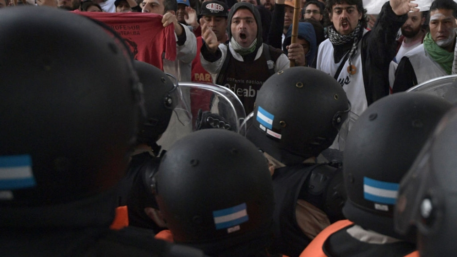 Demonstrators shout slogans against members of Prefectura Naval Argentina who guard the entrance of Pueyrredon bridge in Avellaneda, Buenos Aires on April 6, 2017, during a 24 hours general strike. A 24 hours general strike was called by worker's unions demanding to President Mauricio Macri's government to take measures against inflation and keep campaign promises. / AFP PHOTO / JUAN MABROMATA (Photo credit should read JUAN MABROMATA/AFP/Getty Images)