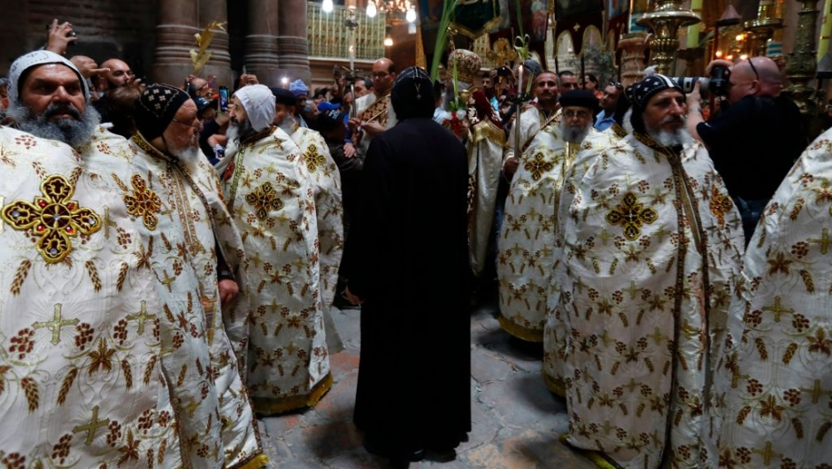 Egyptian Coptic priests encircle the aedicule during the Palm Sunday Easter procession at the Church of the Holy Sepulchre in Jerusalem's Old City on April 9, 2017. The ceremony is a landmark in the Roman Catholic calendar, marking the triumphant return of Christ to Jerusalem the week before his death, when a cheering crowd greeted him waving palm leaves. Palm Sunday marks the start of the most solemn week in the Christian calendar. / AFP PHOTO / GALI TIBBON (Photo credit should read GALI TIBBON/AFP/Getty Images)