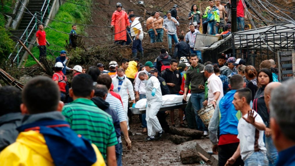 Rescuers carry a corpse after mudslides in Manizales, Caldas department, Colombia on April 19, 2017. Flooding and mudslides in central Colombia have killed at least eleven people, the Red Cross said Wednesday, causing alarm in a country still recovering from mudslides that killed hundreds / AFP PHOTO / STRINGER (Photo credit should read STRINGER/AFP/Getty Images)