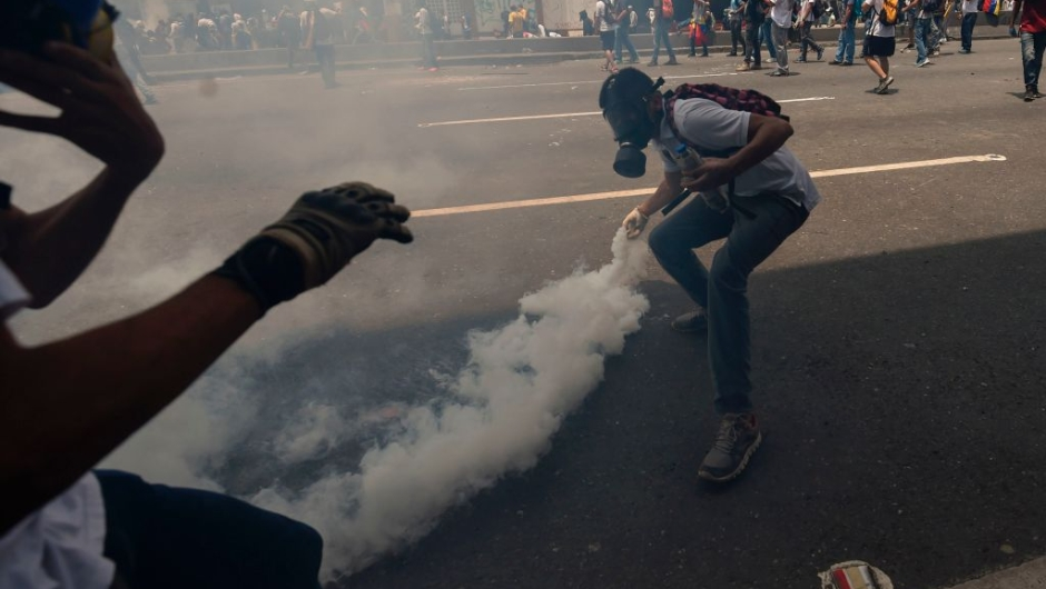 A demonstrator throws a tear gas canister back at the police during a rally against Venezuelan President Nicolas Maduro, in Caracas on April 19, 2017. Venezuela braced for rival demonstrations Wednesday for and against President Nicolas Maduro, whose push to tighten his grip on power has triggered waves of deadly unrest that have escalated the country's political and economic crisis. / AFP PHOTO / Juan BARRETO (Photo credit should read JUAN BARRETO/AFP/Getty Images)