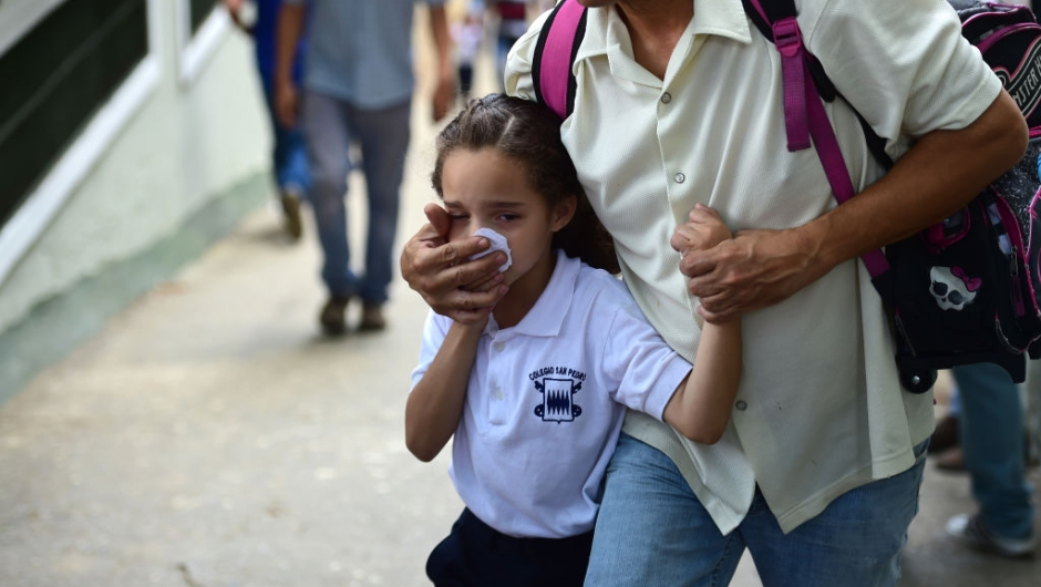 TOPSHOT - A schoolgirl covers her nose and mouth to avoid breathing tear gas shot by police at opponents of Venezuelan President Nicolas Maduro marching in Caracas on April 26, 2017. Protesters in Venezuela plan a high-risk march against President Maduro Wednesday, sparking fears of fresh violence after demonstrations that have left 26 dead in the crisis-wracked country. / AFP PHOTO / RONALDO SCHEMIDT (Photo credit should read RONALDO SCHEMIDT/AFP/Getty Images)