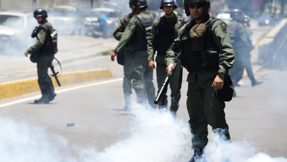 Riot police stand amid a cloud of tear gas on opponents of Venezuelan President Nicolas Maduro marching in Caracas on April 26, 2017. Protesters in Venezuela plan a high-risk march against President Maduro Wednesday, sparking fears of fresh violence after demonstrations that have left 26 dead in the crisis-wracked country. / AFP PHOTO / RONALDO SCHEMIDT (Photo credit should read RONALDO SCHEMIDT/AFP/Getty Images)