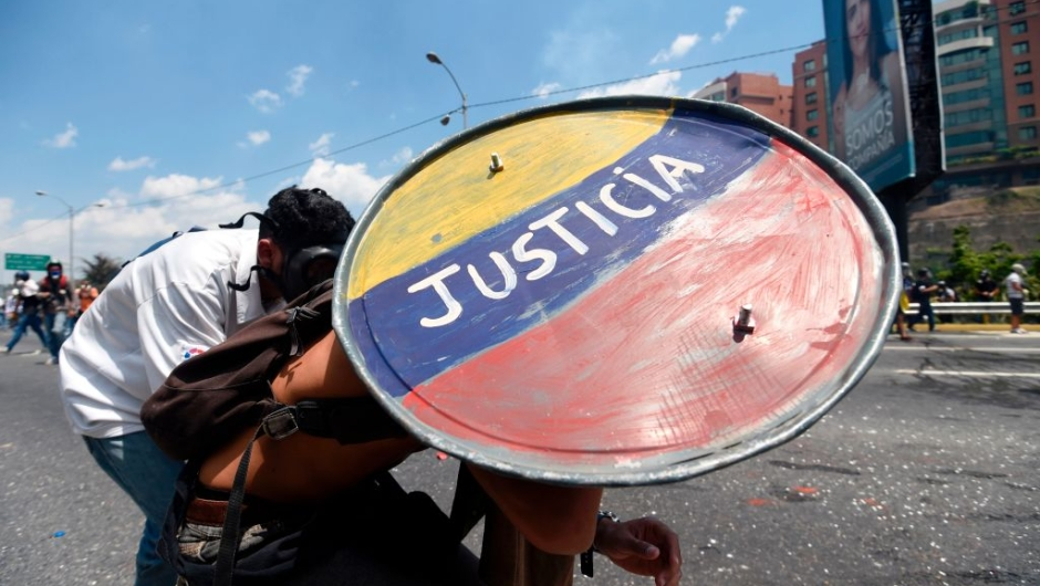 "Opposition demonstrators clash with riot police during a march in Caracas on April 26, 2017. Protesters in Venezuela plan a high-risk march against President Maduro Wednesday, sparking fears of fresh violence after demonstrations that have left 26 dead in the crisis-wracked country. The placard reads ""Jailed Students and Loose Delinquents"" / AFP PHOTO / JUAN BARRETO (Photo credit should read JUAN BARRETO/AFP/Getty Images)"