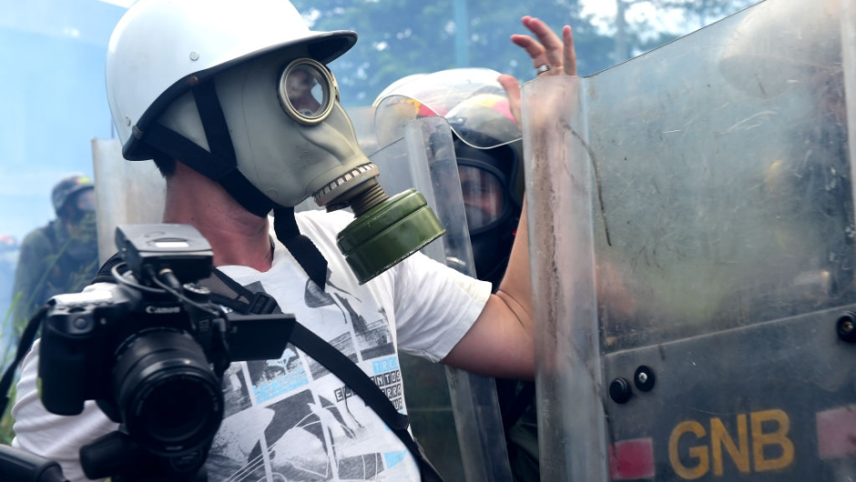 A journalists argues with riot police as opposition activists clash with police during a protest march in Caracas on April 26, 2017. Protesters in Venezuela plan a high-risk march against President Maduro Wednesday, sparking fears of fresh violence after demonstrations that have left 26 dead in the crisis-wracked country. / AFP PHOTO / RONALDO SCHEMIDT (Photo credit should read RONALDO SCHEMIDT/AFP/Getty Images)