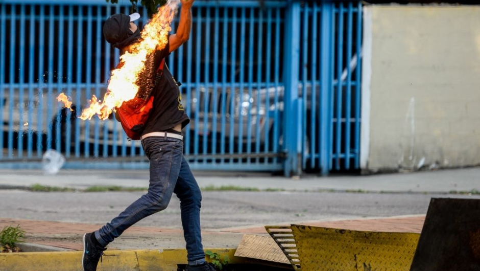 An opposition activist clashes with riot police during a protest against President Nicolas Maduro in Caracas on April 26, 2017. Venezuelan riot police fired tear gas to stop anti-government protesters from marching on central Caracas, the latest clash in a wave of unrest that, up to now, has left 26 people dead. / AFP PHOTO / FEDERICO PARRA (Photo credit should read FEDERICO PARRA/AFP/Getty Images)