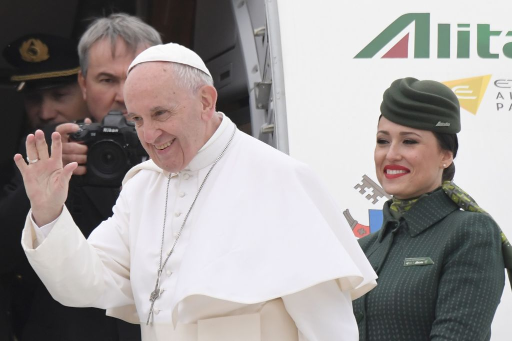 Pope Francis waves to the press as he is welcomed by Alitalia's personnel prior his flight to Egypt, on April 28, 2017 at Rome's Fiumicino airport. Pope Francis heads for a two-day visit in Egypt for talks with the grand imam of the capital's famed Al-Azhar mosque in Cairo, but also to show solidarity with Coptic Christians targeted by violence in Egypt. / AFP PHOTO / Tiziana FABI (Photo credit should read TIZIANA FABI/AFP/Getty Images)