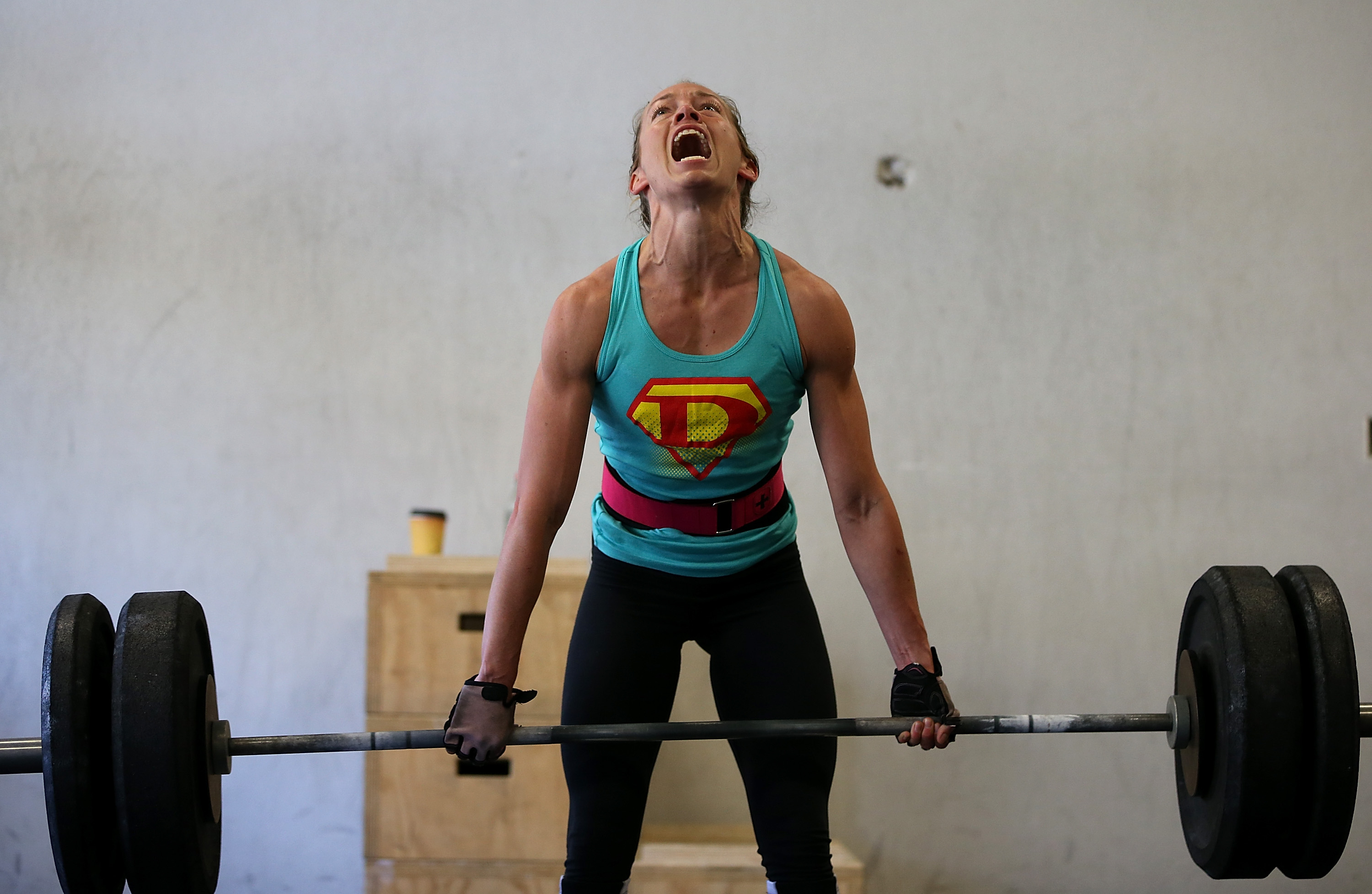 """SAN ANSELMO, CA - MARCH 14: Lita Collins does a deadlift during a CrossFit workout at Ross Valley CrossFit on March 14, 2014 in San Anselmo, California. CrossFit, a high intensity workout regimen that is a constantly varied mix of aerobic exercise, gymnastics and Olympic weight lifting, is one of the fastest growing fitness programs in the world. The grueling cult-like core strength and conditioning program is popular with firefighters, police officers, members of the military and professional athletes. Since its inception in 2000, the number of CrossFit affiliates, or """"boxes"""" has skyrocketed to over 8,500 worldwide with more opening every year. (Photo by Justin Sullivan/Getty Images)"""