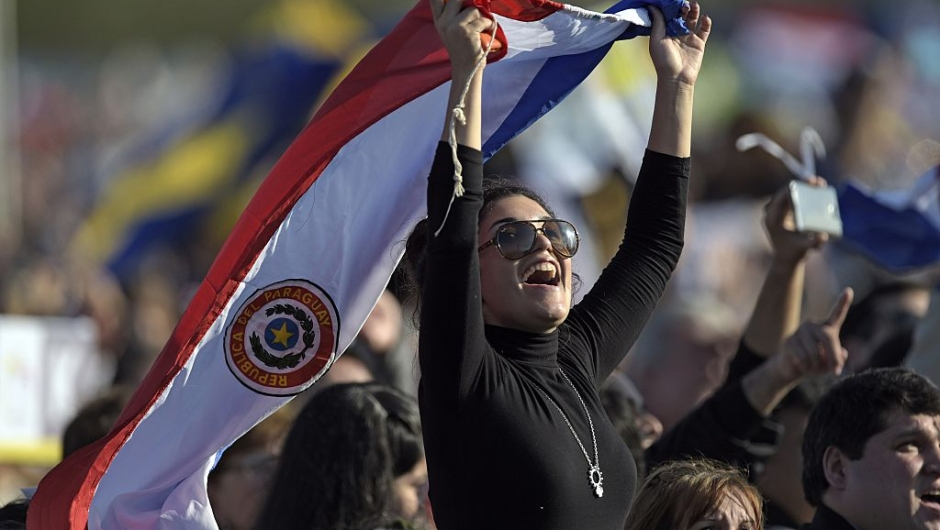 A Catholic faitful holds a Paraguayan national flag as she waits near the altar where Pope Francis will deliver a mass at Nu Guazu field in the outskirts of Asuncion, Paraguay on July 12, 2015. The Pope finishes Sunday his Latin American tour. AFP PHOTO / JUAN MABROMATA (Photo credit should read JUAN MABROMATA/AFP/Getty Images)