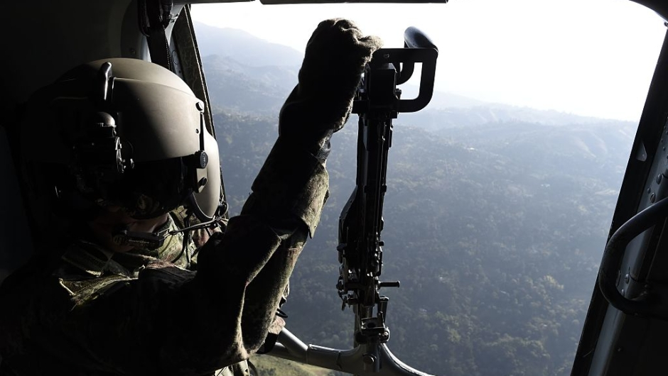 soldier remains on a helicoper as it overflies Valle del cauca department, Colombia on January 24, 2017. French President Francois Hollande visits Tuesday a FARC rebel disarmament zone in support of Colombia's peace process. / AFP / STEPHANE DE SAKUTIN (Photo credit should read STEPHANE DE SAKUTIN/AFP/Getty Images)