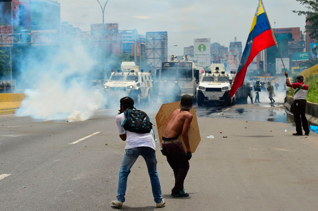 Demonstrators clash with riot police during a protest against Venezuelan President Nicolas Maduro, in Caracas on May 3, 2017. Venezuela's angry opposition rallied Wednesday vowing huge street protests against President Nicolas Maduro's plan to rewrite the constitution and accusing him of dodging elections to cling to power despite deadly unrest. / AFP PHOTO / RONALDO SCHEMIDT (Photo credit should read RONALDO SCHEMIDT/AFP/Getty Images)