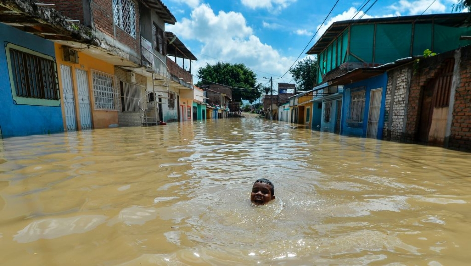 A boy swims in a flooded area of Cali, Colombia, on May 13, 2017 after heavy rains caused the overflowing of the Cauca river. Flooding and mudslides in Colombia have killed several people and affected thousands in the past weeks causing alarm in a country still recovering from recent mudslides that killed hundreds. / AFP PHOTO / LUIS ROBAYO (Photo credit should read LUIS ROBAYO/AFP/Getty Images)